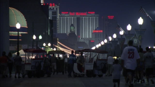 vidéos et rushes de wide angle on people walking and pushing trolleys along the boardwalk. the taj mahal hotel in bg. - allée couverte de planches