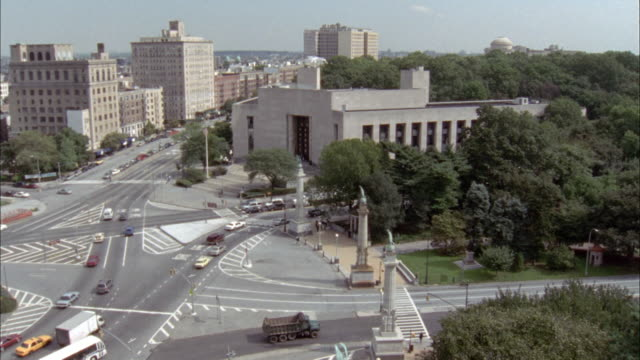 WIDE ANGLE OF BROOKLYN PUBLIC LIBRARY. PAN LEFT AND BACK TOWARD TREE TOPS IN PARK.
