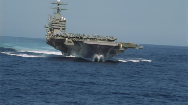 aerial of navy aircraft carrier fly-by. military aircraft and jets fill deck. fa-18 hornets, e-2c hawkeyes, s-3b vikings visible. military personnel move and work on deck. ship rises and falls on waves on pacific ocean. - aircraft carrier stock videos & royalty-free footage