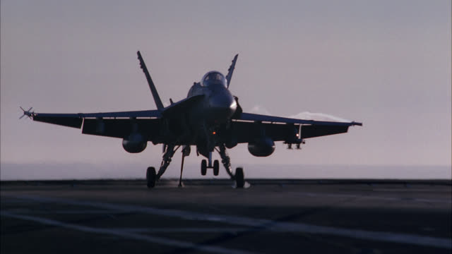 vídeos de stock, filmes e b-roll de hand held of fa-18 hornet fighter jet landing on deck of navy aircraft carrier. military personnel move and work on deck. hornet hitches arresting cable. airplane moves to park and secure. - cable