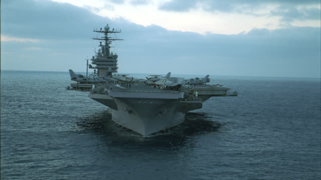 aerial of navy aircraft carrier. fa-18 hornet fighter jets, e-2c hawkeye reconnaissance military airplanes and s-3b viking anti-submarine jets parked and secured to deck. steam rises from take-off catapult. military personnel move and work on deck. connin - aircraft carrier stock videos & royalty-free footage