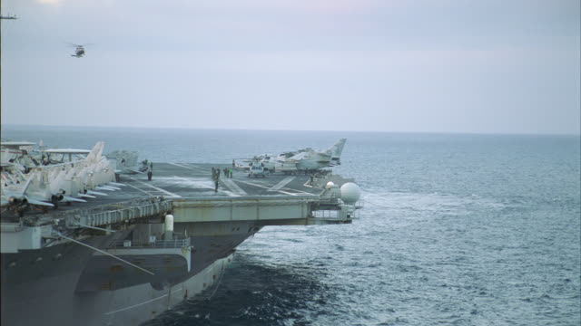 aerial of navy aircraft carrier. fa-18 hornet fighter jets, e-2c hawkeye reconnaissance military airplanes and s-3b viking anti-submarine jets parked and secured to deck. steam rises from take-off catapult. helicopter hovers over ship. military personnel - aircraft carrier stock videos & royalty-free footage
