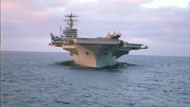 AERIAL OF NAVY AIRCRAFT CARRIER. FA-18 HORNET FIGHTER JETS, E-2C HAWKEYE RECONNAISSANCE MILITARY AIRPLANES AND S-3B VIKING ANTI-SUBMARINE JETS PARKED AND SECURED TO DECK. STEAM RISES FROM TAKE-OFF CATAPULT. MILITARY PERSONNEL MOVE AND WORK ON DECK. CONNIN