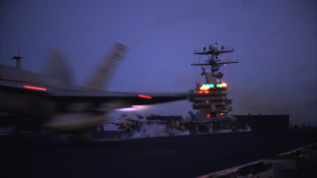 wide angle of fa-18 hornet fighter jet take-off from deck of navy aircraft carrier. military personnel move and work on deck. miscellaneous equipment visible. ship rises and falls on waves on pacific ocean. - navy stock videos & royalty-free footage