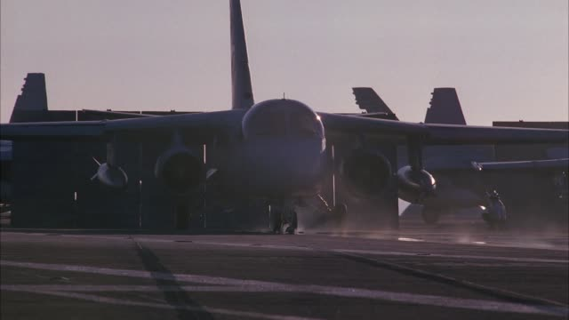 HAND HELD OF S-3B VIKING MILITARY JET TAKE-OFF FROM DECK OF NAVY AIRCRAFT CARRIER. BLAST SHIELD RAISED. STEAM RISES FROM CATAPULT. MILITARY PERSONNEL MOVE AND WORK ON DECK. FA-18 HORNETS PARKED AND SECURED TO DECK. SHIP RISES AND FALLS ON WAVES ON PACIFIC
