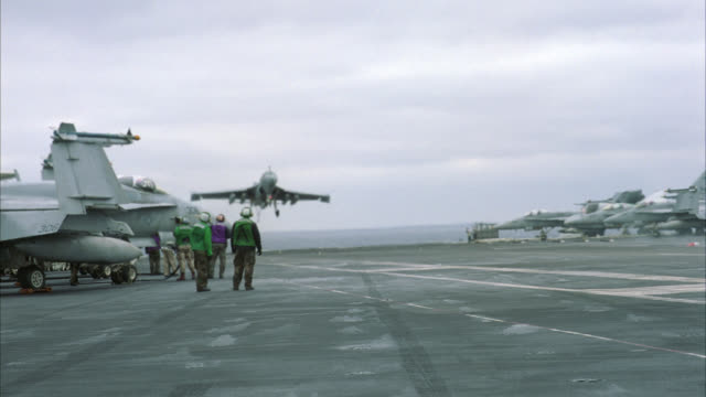 HAND HELD OF S-3B VIKING MILITARY JET LANDING ON DECK OF NAVY AIRCRAFT CARRIER. JET BRAKES USING ARRESTING GEAR. MILITARY PERSONNEL MOVE AND WORK ON DECK. MILITARY AIRPLANE IN FG. SHIP RISES AND FALLS ON WAVES ON PACIFIC OCEAN. CLOUDY SKY.