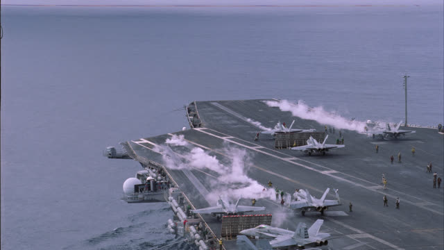 aerial of deck of navy aircraft carrier. military fa-18 hornet fighter jets ready for take-off. military personnel move and work on deck. miscellaneous equipment visible. steam rises from catapults. - aircraft carrier stock videos & royalty-free footage