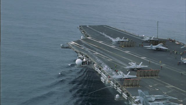 AERIAL OF DECK OF NAVY AIRCRAFT CARRIER. MILITARY FA-18 HORNET FIGHTER JETS TAKE-OFF. S-3B VIKING TAXIING ON DECK. MILITARY PERSONNEL MOVE AND WORK ON DECK. MISCELLANEOUS EQUIPMENT VISIBLE. STEAM RISES FROM CATAPULTS.