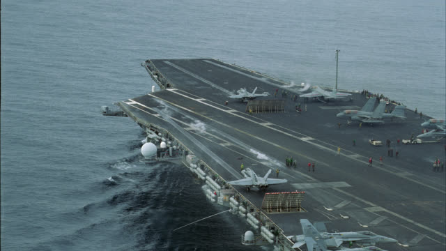 AERIAL OF  FA-18 HORNET FIGHTER JETS TAKE-OFF FROM DECK OF NAVY AIRCRAFT CARRIER. S-3B VIKING TAXIING ON DECK. MILITARY PERSONNEL MOVE AND WORK ON DECK. MISCELLANEOUS EQUIPMENT VISIBLE. STEAM RISES FROM CATAPULTS.