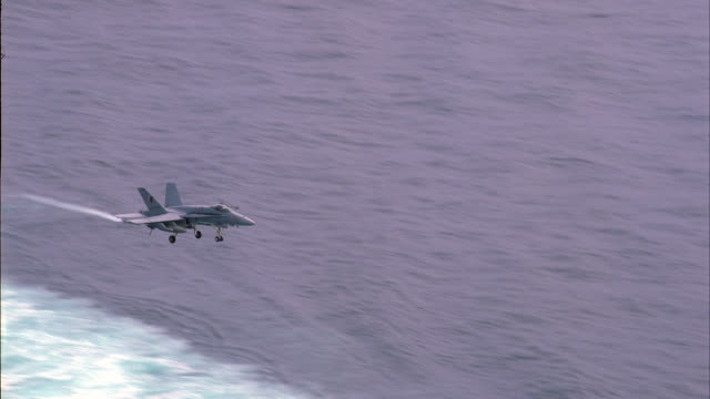 AERIAL OF FA-18 HORNET FIGHTER JET LANDING ON DECK OF NAVY AIRCRAFT CARRIER. MILITARY PERSONNEL MOVE AND WORK ON DECK. FA-18 HORNETS, E-2C HAWKEYES AND S-3B VIKING MILITARY JETS PARKED AND SECURED ON DECK.