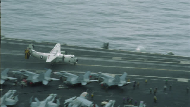AERIAL OF E-2C MILITARY AIRPLANE LANDING ON DECK OF NAVY AIRCRAFT CARRIER. MILITARY PERSONNEL MOVE AND WORK ON DECK. FA-18 HORNETS, E-2C HAWKEYES AND S-3B VIKING MILITARY JETS PARKED AND SECURED ON DECK.