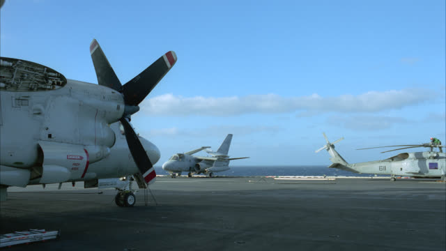 PAN LEFT TO RIGHT OF ACTIVITY ON DECK OF NAVY AIRCRAFT CARRIER. FA-18 HORNET FIGHTER JETS, E-2C HAWKEYE PROPELLER PLANES,  S-3B VIKING MILITARY JETS, MILITARY HELICOPTER AND VARIOUS EQUIPMENT PARKED AND SECURED TO DECK. MILITARY PERSONNEL MOVE EXTERNAL FU