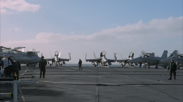 WIDE ANGLE OF ACTIVITY ON DECK OF NAVY AIRCRAFT CARRIER. FA-18 HORNET FIGHTER JETS AND S-3B VIKING MILITARY AIRPLANES PARKED AND SECURED TO DECK. MILITARY PERSONNEL MOVE AND WORK ON DECK. ARRESTING BRAKE CABLES LINE DECK. SHIP RISES AND FALLS ON WAVES ON