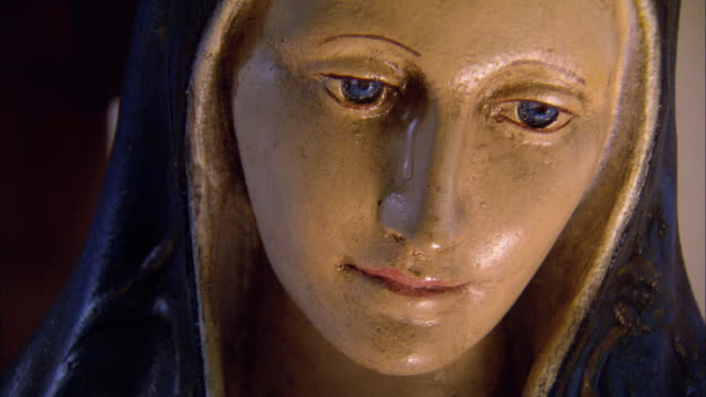 CLOSE ANGLE OF VIRGIN MARY STATUE SIDE PROFILE. CAMERA ZOOMS IN ON FACE AS TEAR FALLS DOWN HER CHEEK. COULD BE USED FOR MIRACLE.