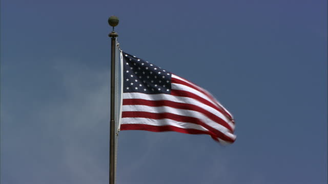 ms. looking up at american flag on flagpole, waving in the wind. - stars and stripes stock videos & royalty-free footage