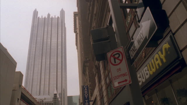 up angle. one ppg place building in bg. 'no parking' and 'one way' street signs and 'subway' sign in fg. - no parking sign stock videos & royalty-free footage