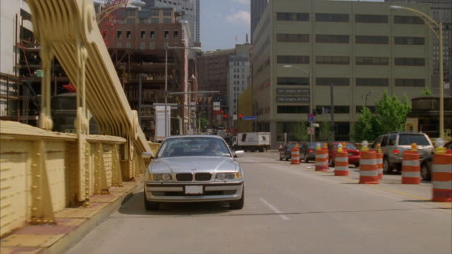 pan down. driving down city street. pans down to silver bmw following camera. camera and bmw turn left onto roberto clemente bridge. pans right to downtown pittsburgh in bg. pans back to bmw - bmw stock videos & royalty-free footage