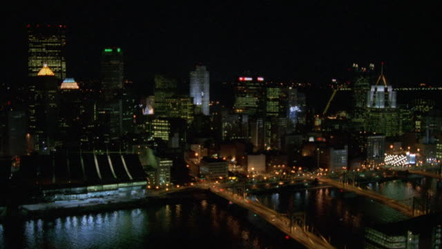 AERIAL OF DOWNTOWN PITTSBURGH SKYLINE. PANS ACROSS CITY BORDERING THE RIVER WITH THE BRIDGES LIT UP ON THE ALLEGHENY RIVER. PANS OVER PNC PARK BASEBALL STADIUM.