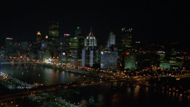 AERIAL OF DOWNTOWN PITTSBURGH SKYLINE. PANS ACROSS CITY BORDERING THE RIVER WITH THE BRIDGES LIT UP ON THE MONONGAHELA RIVER.  PANS PAST THE PNC PARK STADIUM