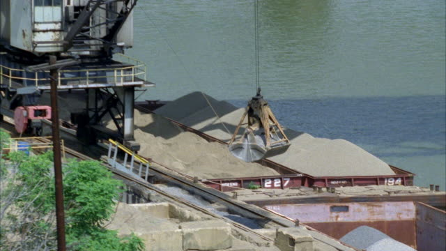 vídeos de stock e filmes b-roll de wide angle of construction site as crane attempts to lift sand or cement from bin.  carries it out as camera pans left to right to pittsburgh skyline behind the allegheny river. - cimento