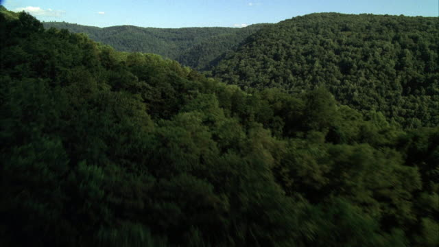 aerial over treetops and hilltops.  flies across green mountains and hills separated by a river. - pennsylvania stock videos and b-roll footage
