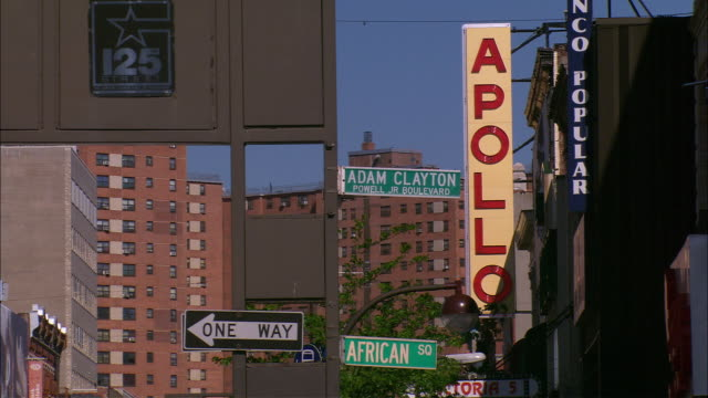 """medium angle of a street sign in harlem that reads """"adam clayton powell jr boulevard"""". another sign reads """"apollo"""", for the apollo theater, - harlem stock videos & royalty-free footage"""
