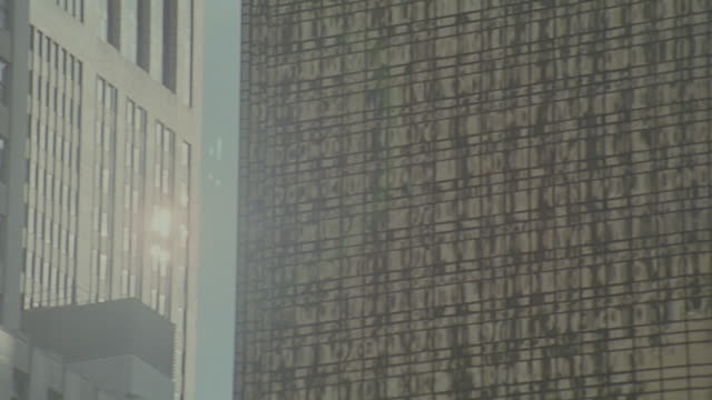 up angle of two multi-story or high rise buildings with glass windows. could be office buildings. camera pans back and forth between buildings. sun reflects off windows. blue sky with white clouds. - blue glass stock videos and b-roll footage