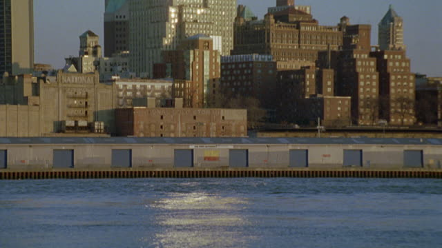 medium angle of water rippling in east river. camera pans up to multi-story and high rise buildings of new york city skyline. sun reflecting off glass office buildings and blue sky above. - 2005 stock videos and b-roll footage