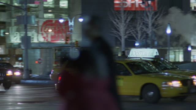 "medium angle of  taxis and cars in traffic driving down new york city street. building with many windows in bg. camera follows flow of traffic to right of screen. bare trees. glass-windows of department stores of plaza lit at night. ""borders"" sign above "" - 2005 stock videos & royalty-free footage"