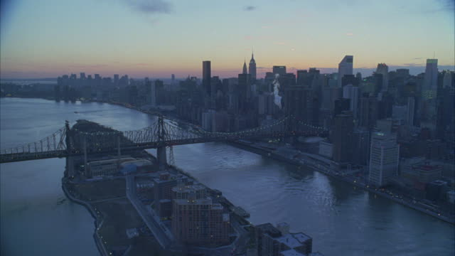 aerial of new york city skyline. see queensboro bridge over east river and roosevelt island. see skyscrapers and high rise buildings frame right. steam from power plant smokestack or other building. - steam stock videos & royalty-free footage
