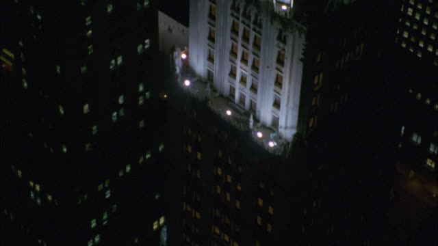 AERIAL VIEW OF WOOLWORTH BUILDING IN NW YORK CITY AT NIGHT. TRAVEL UP BUILDING AND BIRDSEYE VIEW OVER ROOFTOP, SEE GREEN AND WHITE LIGHTS AND ILLUMINATED TOP FLOORS OF BUILDING. SEE MULTI-STORY, OFFICE AND HIGH RISE BUILDINGS IN BG. SKYSCRAPERS.