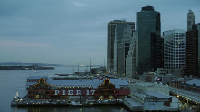 pan left to right of new york city pier 17. staten island ferry boat in east river. support pillar of brooklyn bridge frame left. camera pans right to show 120 wall street building, continental center, one seaport plaza, citibank building, and one financi - entertainment center stock videos and b-roll footage