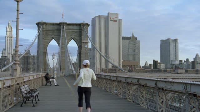 WIDE ANGLE OF NEW YORK CITY SKYLINE.  BROOKLYN BRIDGE IN FG. CAMERA FROM PEDESTRIAN PATH FACING DIRECTLY DOWN PATH OF BRIDGE. VERIZON LOGO ON BUILDING IN BG. OTHER SKYSCRAPERS AND HIGH RISE BUILDINGS IN BG. PERSON SITTING ON BENCH ON BRIDGE. JOGGER RUN AW