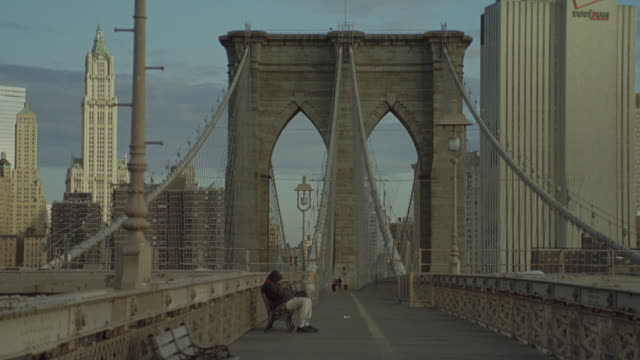 pan right to left of new york city skyline. brooklyn bridge in fg. camera from pedestrian path facing directly down path of bridge. verizon logo on building in bg. other skyscrapers and high rise buildings in bg. see person sitting on bench on bridge. cam - brooklyn bridge stock videos & royalty-free footage