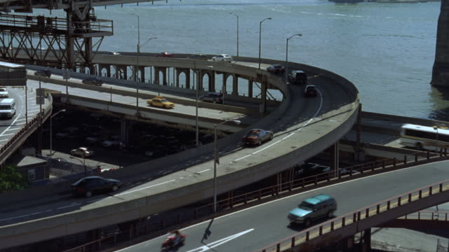 pan up from roosevelt highway under next to east river to brooklyn bridge. cars and trucks drive on road. city in bg. american flag on top of bridge. - pan american highway video stock e b–roll