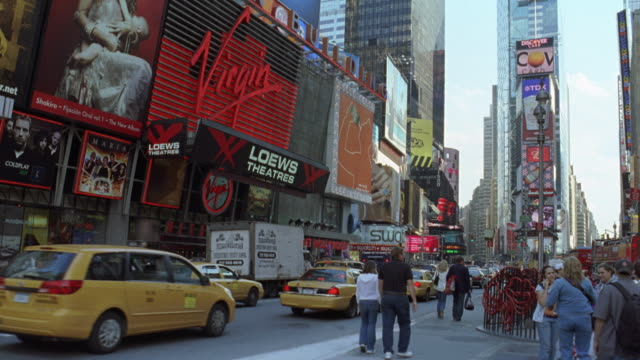 medium angle of times square. cars, taxis, and tour buses driving on city street. advertisements and billboards on side of stores and buildings. virgin records logo left of frame. pedestrians on sidewalk. neon signs. - theatre district stock videos & royalty-free footage