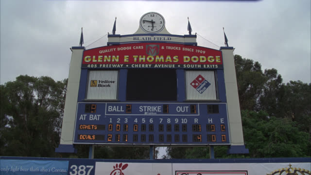 """wide angle of a baseball scoreboard and digital display at blair field in long beach, california. score shows 2-0 for the """"devils"""" over the """"comets."""" various advertisements displayed, including """"glenn e thomas dodge,"""" """"yellow book"""" and """"domino's."""" trees a - e book stock videos & royalty-free footage"""