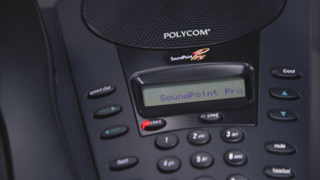 """CLOSE ANGLE OF A SOUNDPOINT PRO POLYCOM CONFERENCE PHONE. DISPLAY SHOWS """"SOUNDPOINT PRO,"""" LINE 1 FLASHES RED, """"NO ID MESSAGE"""" DISPLAYS, LINE 1 TURNS GREEN, RECEIVER IS LIFTED, THEN FLASHES AS IF PLACED ON HOLD. OFFICE EQUIPMENT."""