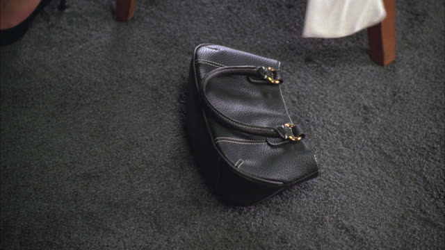 close angle of a woman's hands grabbing and picking up a purse or handbag from under a table and scrambling, searching for, or organizing something in her purse. high heeled shoes visible. - speisezimmer stock-videos und b-roll-filmmaterial