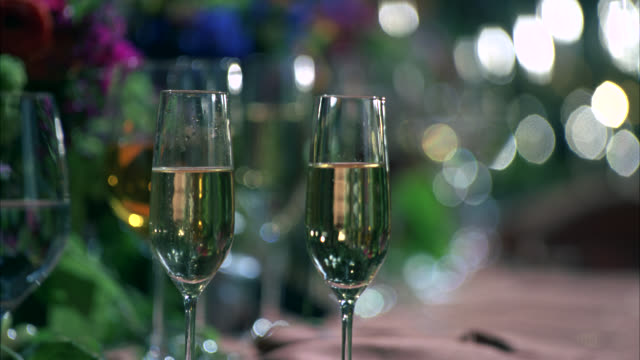close angle of champagne flute glasses filled with sparkling white wine or champagne. man's hand picks up one of the glasses as if to take a sip. colorful backdrop becomes out of focus for visual effect. person places glass back on table. could be new yea - visual effect stock videos & royalty-free footage