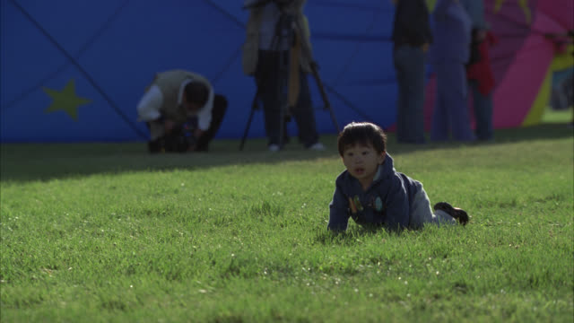 PAN RIGHT TO LEFT OF LITTLE BOY OR BABY CRAWLING IN GRASS AT A PARK. CHILDREN OR KIDS. WOMAN OR MOTHER PICKS HIM UP. HOT AIR BALLOON BEING INFLATED IN BG. COULD BE AT FAIR OR FESTIVAL.