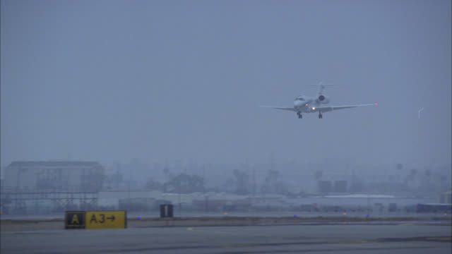 stockvideo's en b-roll-footage met pan right to left of airplane, private jet, landing on runway at los angeles international airport, lax. overcast, cloudy day. high rise hotels in bg. - lax airport