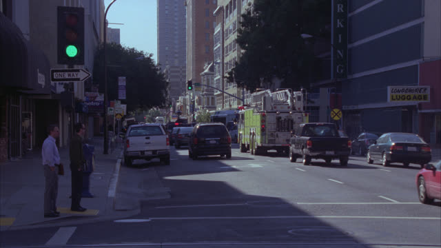 medium angle of cars driving on city street. pedestrians visible. trees line street. fire engines. suvs. - sacramento stock videos & royalty-free footage