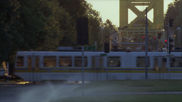 wide angle of downtown sacramento. pedestrians walking along green grassy area. trees. intersections. sprinklers in fg. light rail train moves by. tower bridge in bg. - sacramento stock videos & royalty-free footage
