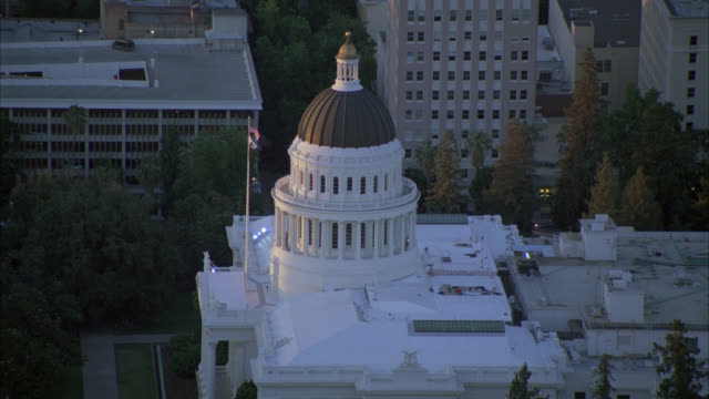 AERIAL OVER CITY OF SACRAMENTO. CAMERA FOCUSES ON DOMED BUILDING. COULD BE CITY HALL OR COURTHOUSE. AMERICAN FLAG. TREES. HIGH RISES AND OFFICE BUILDINGS.  CALIFORNIA STATE CAPITOL BUILDING. GOVERNMENT BUILDING.