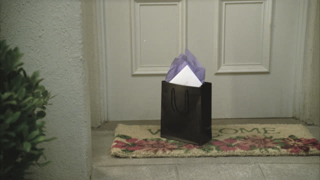 close angle of present or gift bag with card sitting on welcome mat at front door to apartment or house. - welcome mat stock videos and b-roll footage