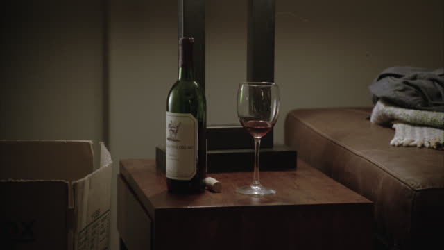 close angle of wine bottle and wine glass sitting on side table. cardboard box visible next to side table. - wine glass stock videos & royalty-free footage