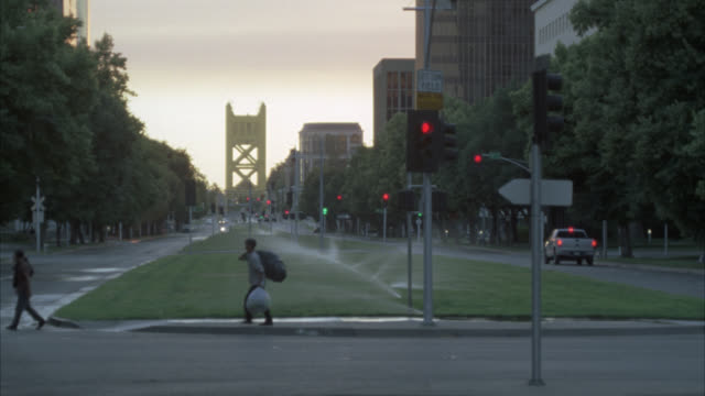 WIDE ANGLE OF SPRINKLERS WATERING GRASS OF CALIFORNIA STATE CAPITOL MALL. TOWER BRIDGE IN BG. PEOPLE OR PEDESTRIANS WALKING ON SIDEWALKS OF CITY STREETS. STOPLIGHTS OR TRAFFIC SIGNALS. SUNSET.