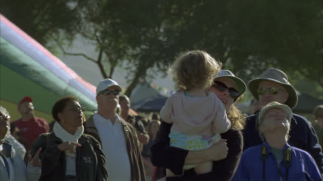 MEDIUM ANGLE OF WOMAN OR MOTHER HOLDING DAUGHTER, GIRL, CHILD OR TODDLER. CROWD OF PEOPLE IN PARK, COULD BE FAIR OR FESTIVAL.