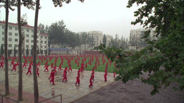PAN UP OF MEN, TEACHERS AND BOYS, STUDENTS, IN COURTYARD OR PARK PRACTICING MARTIAL ARTS. COULD BE KUNG FU. HIGH RISE APARTMENT BUILDINGS IN BG.